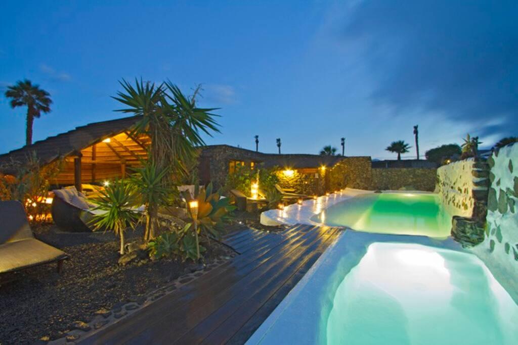 Shared pool area at night at Finca De arrieta