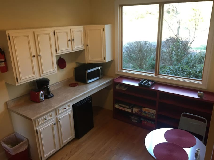 kitchenette with coffee maker, microwave, fridge, silverware, cups and dishes, and sink(in the laundry room)