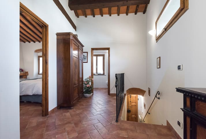 Upstairs landing: bedroom on the left, bathroom straight ahead and staircase to the right. The rich deep brown-red tiles are an attractive Tuscan feature.