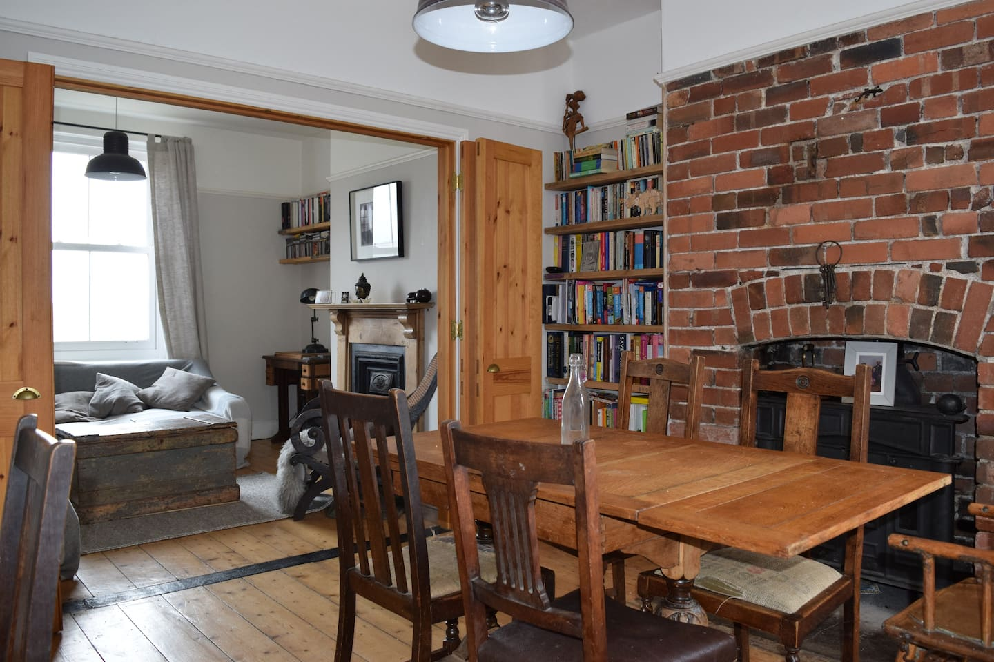 Dining room leading to the living room. Dining room has wood burner