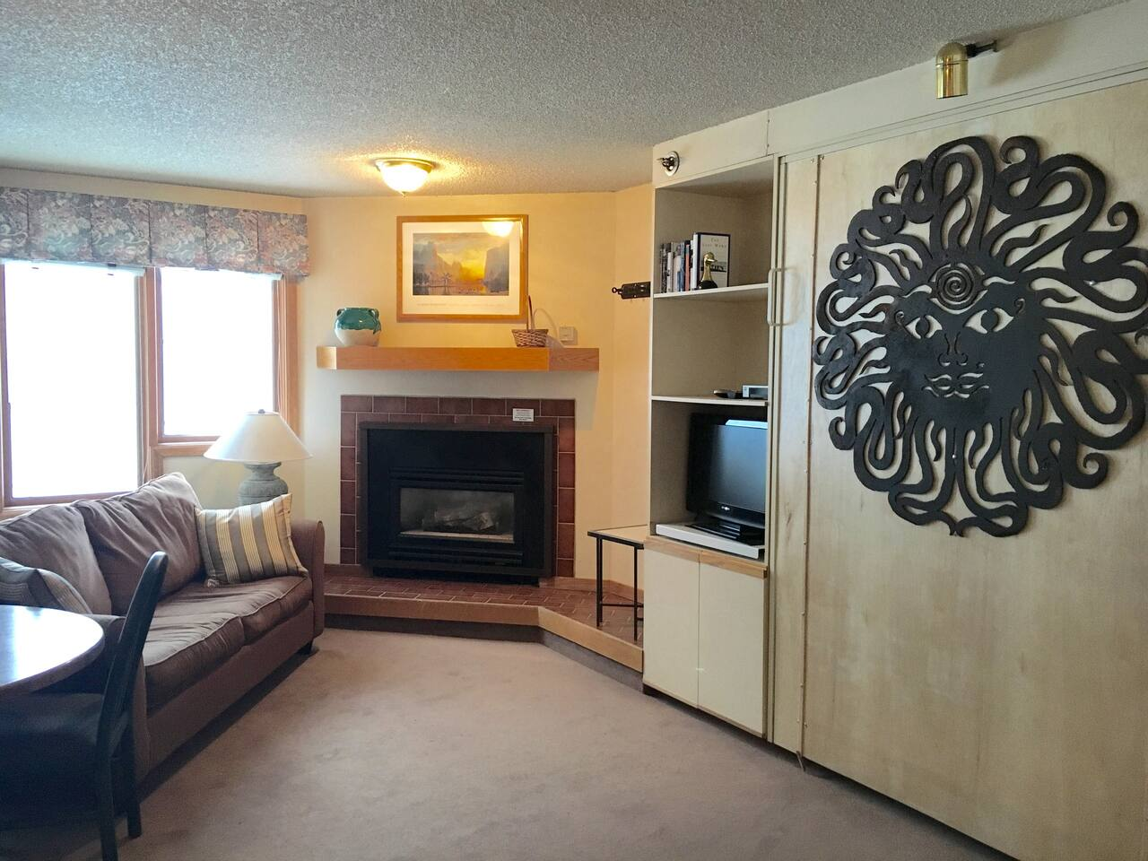 Gas fireplace provides comfy heat, metal art on murphy bed, pull out sofa