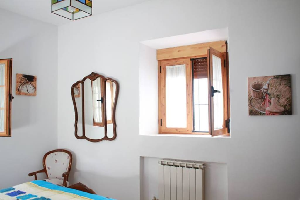 Dormitorio principal, mesitas de noche, armario, espejo, butaca. Con vistas a la calle, al patio de la casa y zona verde.