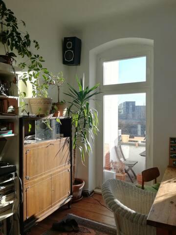 Wohnzimmer mit Balkon, großem Tisch und einer Matratze zum Schlafen