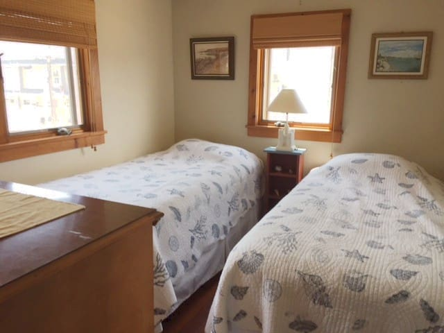 Second bedroom with two twin beds and windows looking to the beach.