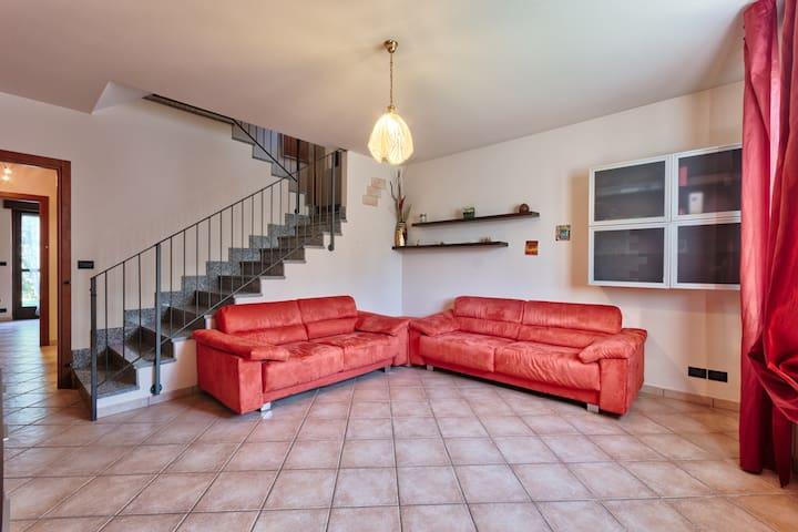 Scala a vista su soggiorno che porta al piano superiore