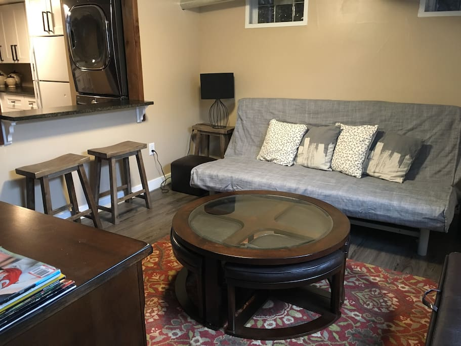 Cozy family room with queen bed, coffee table, bar, window and TV with Roku
