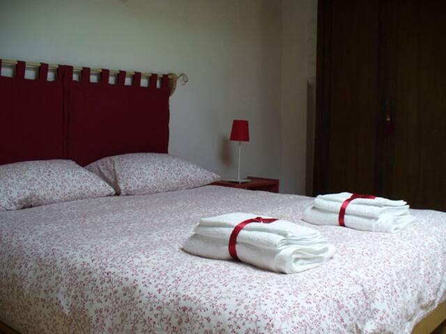 camera matrimoniale nel soppalco, letto king size, travi a vista, pavimento legno,armadio in stile