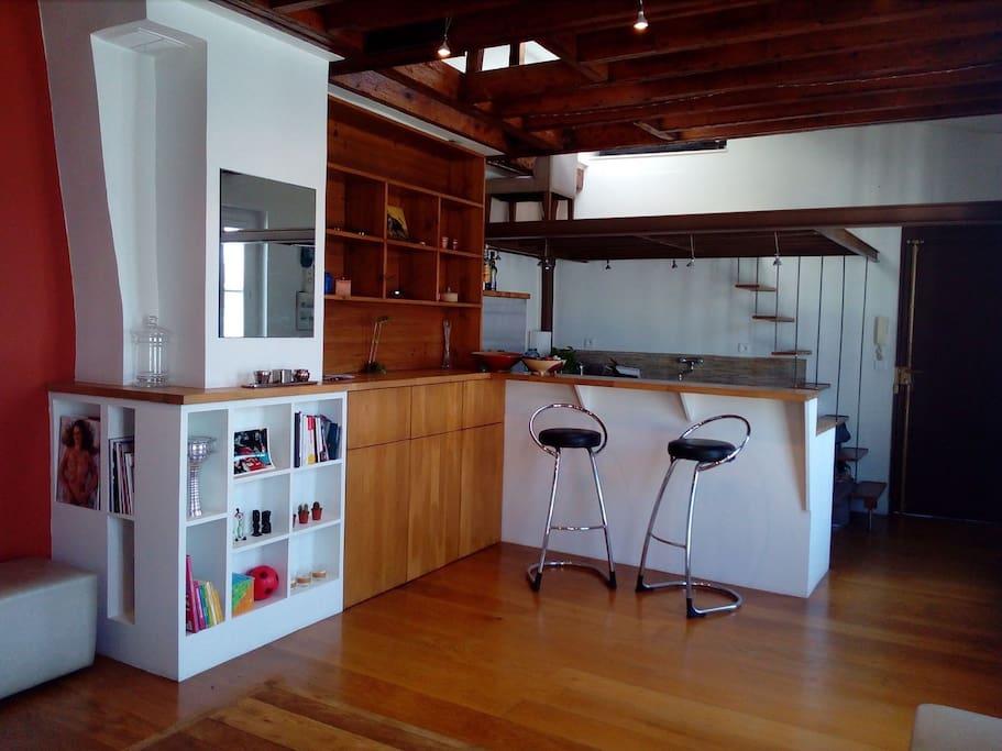 Vue du salon et de la cuisine. Vue de la mezzanine où se trouve l'espace bureau.