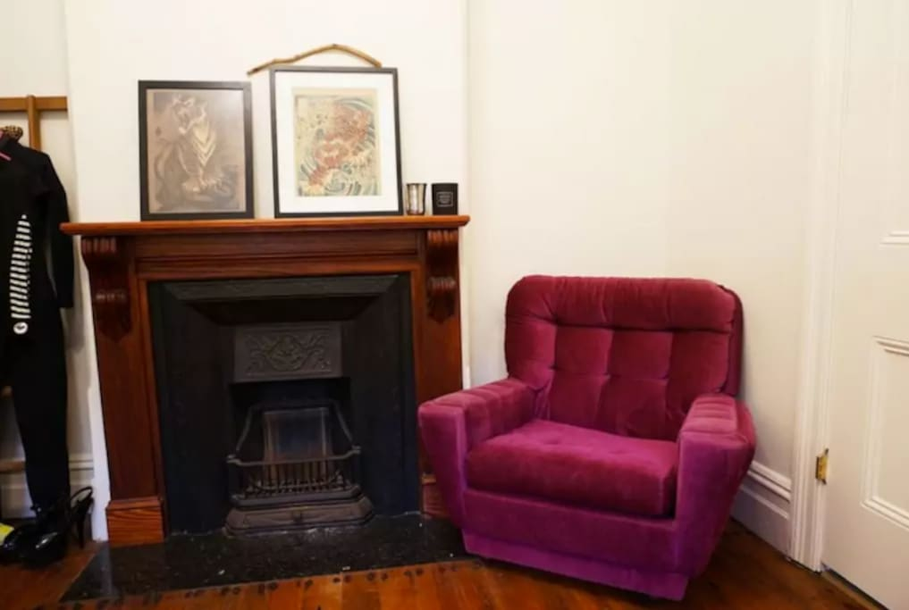Cosy with an old fireplace and a comfy [if ugly] pink lounge.