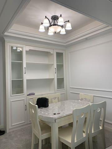 干净整洁的餐厅。餐桌可以展开成圆桌,旁边有精致的酒柜(半手工)。