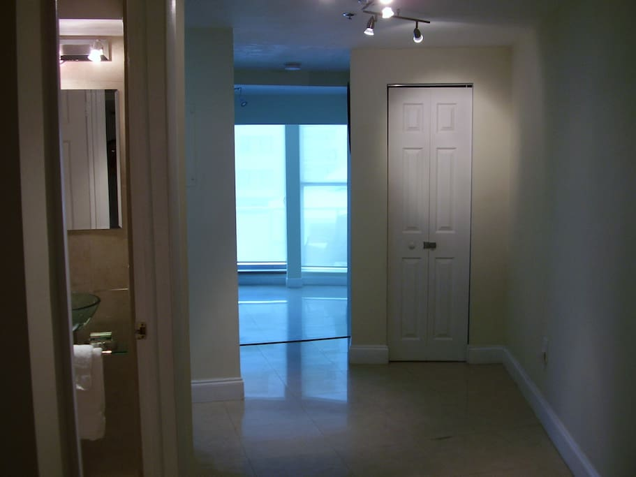 Hallway entering the apartment 2nd bathroom to your left sunken living room just ahead