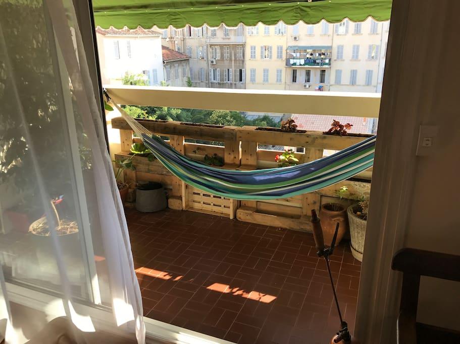 Vue de la terrasse qui donne sur un coeur d'îlot végétalisé et sur le salon-salle à manger, cuisine. Il est orienté ouest et est composé d'une table ainsi que d'un store. Il est très au calme et extrêmement agréable de manger dehors durant la belle saison.
