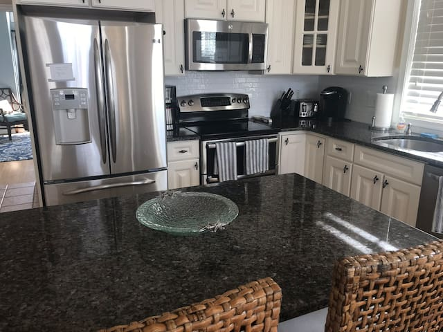 Kitchen with new countertops, stainless steel appliances and essential spices in cabinets.