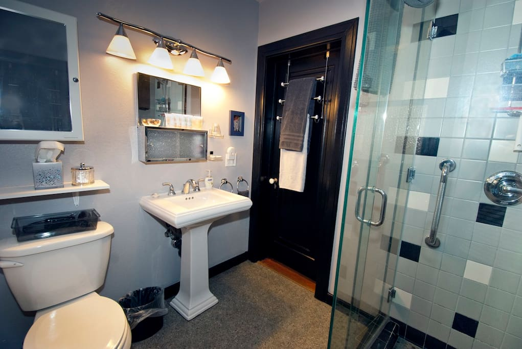 Your bath features a large glass walled shower with safety grab bars.