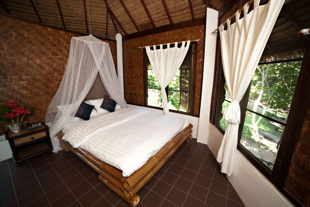 A comfy bed with a mosquito net and fan to keep you cool at night.