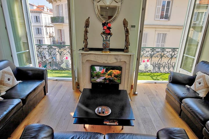 Sejour balcony with artificial turf; AppleTV in the fireplace delivers Youtube, Netflix, Amazon Prime, Apple movies etc. On the mantelpiece is the TV  soundbar and on the right is the central aircon control panel.
