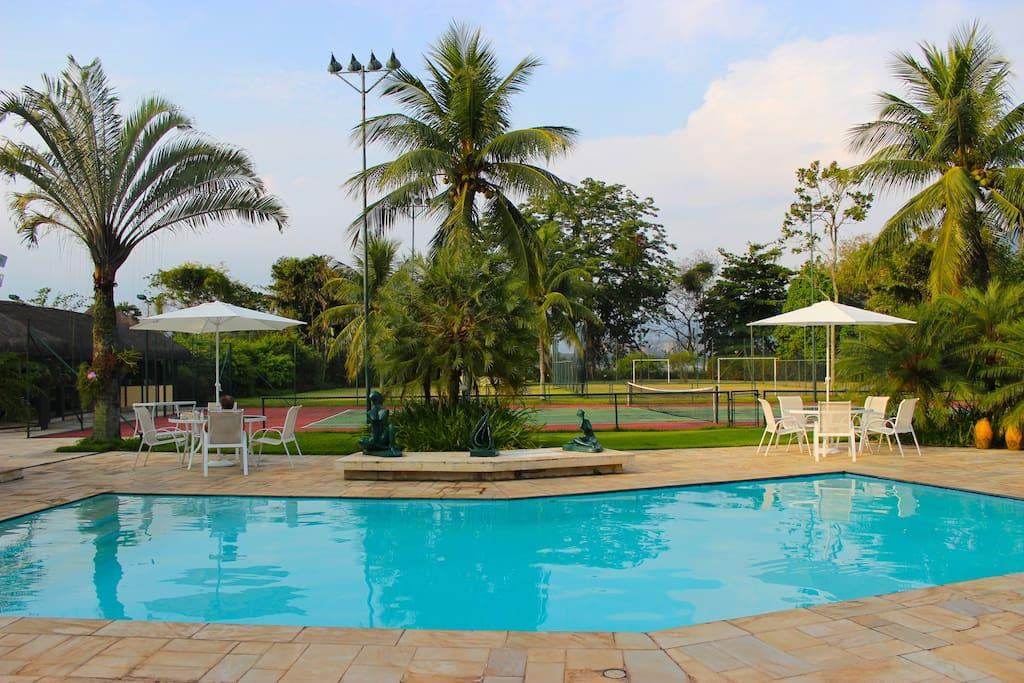 Vista para a piscina, quadra de tênis e campo de futebol.