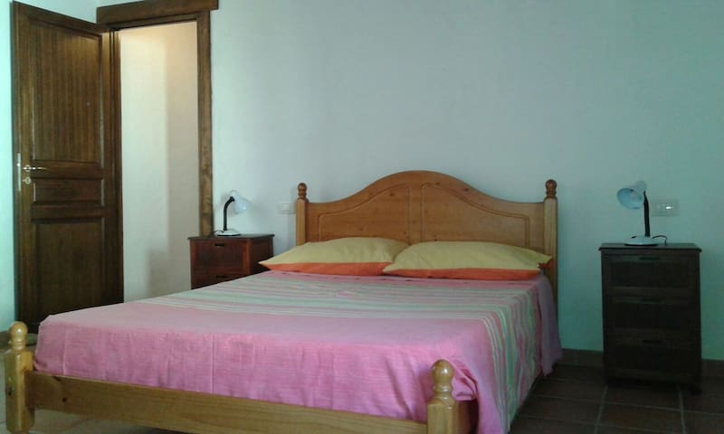 Nice comfortable bed at the cottage apartment in San Benedetto, perfect after a long trekking adventure, or a day on the beach, it has a wood beamed ceiling and a view of the mountain.