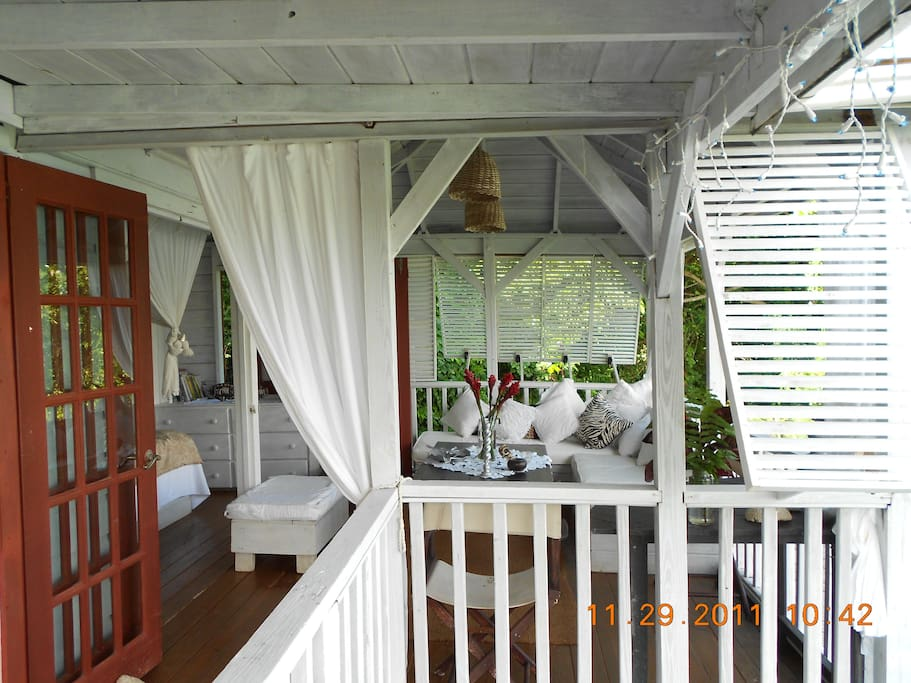 The verandah of Bird House with comfortable lounge area.  Tropical  song birds perch on yourj sugar bowl while you have your first cup of coffee or tea.