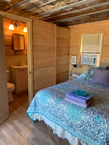 All rooms are located in lofted cabin. Middle room with green door. This room features a full size bed, fluffy pillows, air conditioning, blow dryer, ironing board, coffee pot, bathroom with standup shower. A lovely little self contained cabin room.