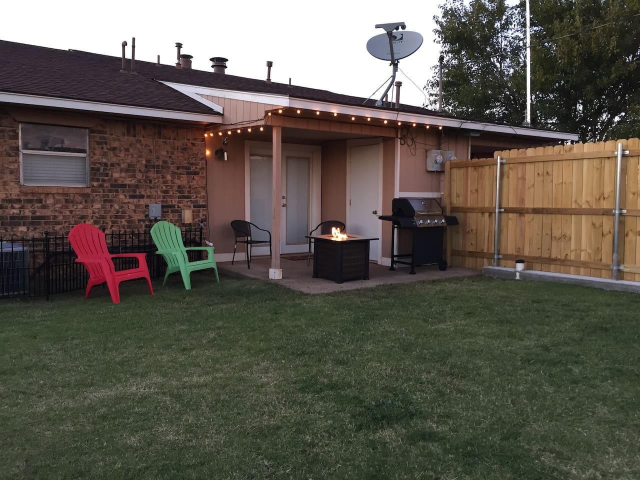 Backyard patio area with gas fire pit and gas grill