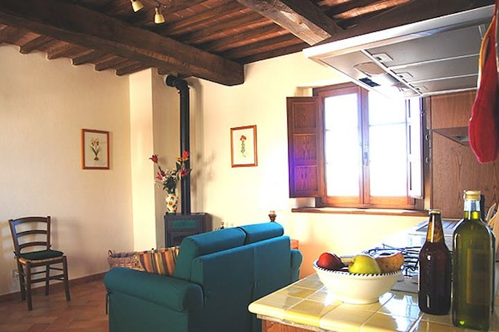 The living room has a wood-burning ceramic stove, a single sofa bed and sat. TV.