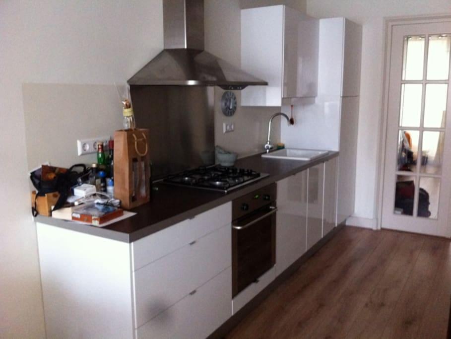 Modern Kitchen with fridge, oven, dishwasher.