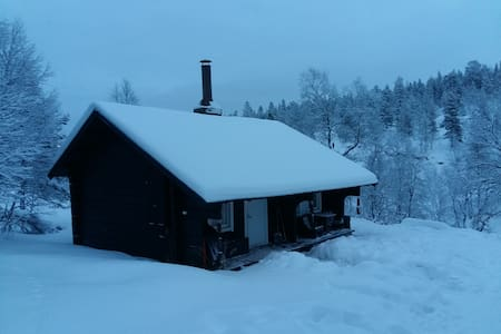 A cozy log cabin next to a mountain creek - Saariselkä