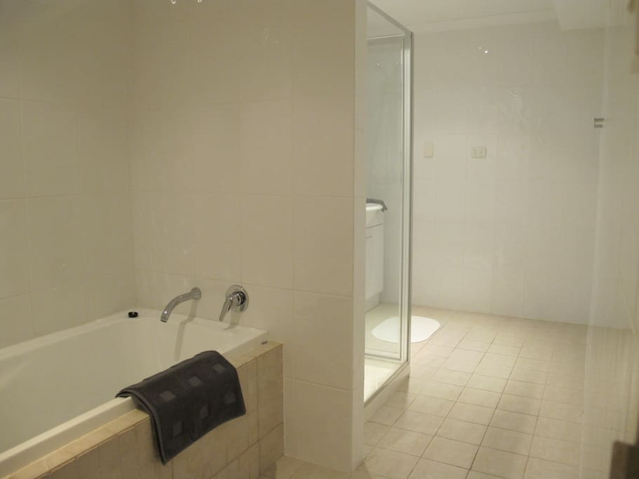 Bathroom with bath, shower and washing machine
