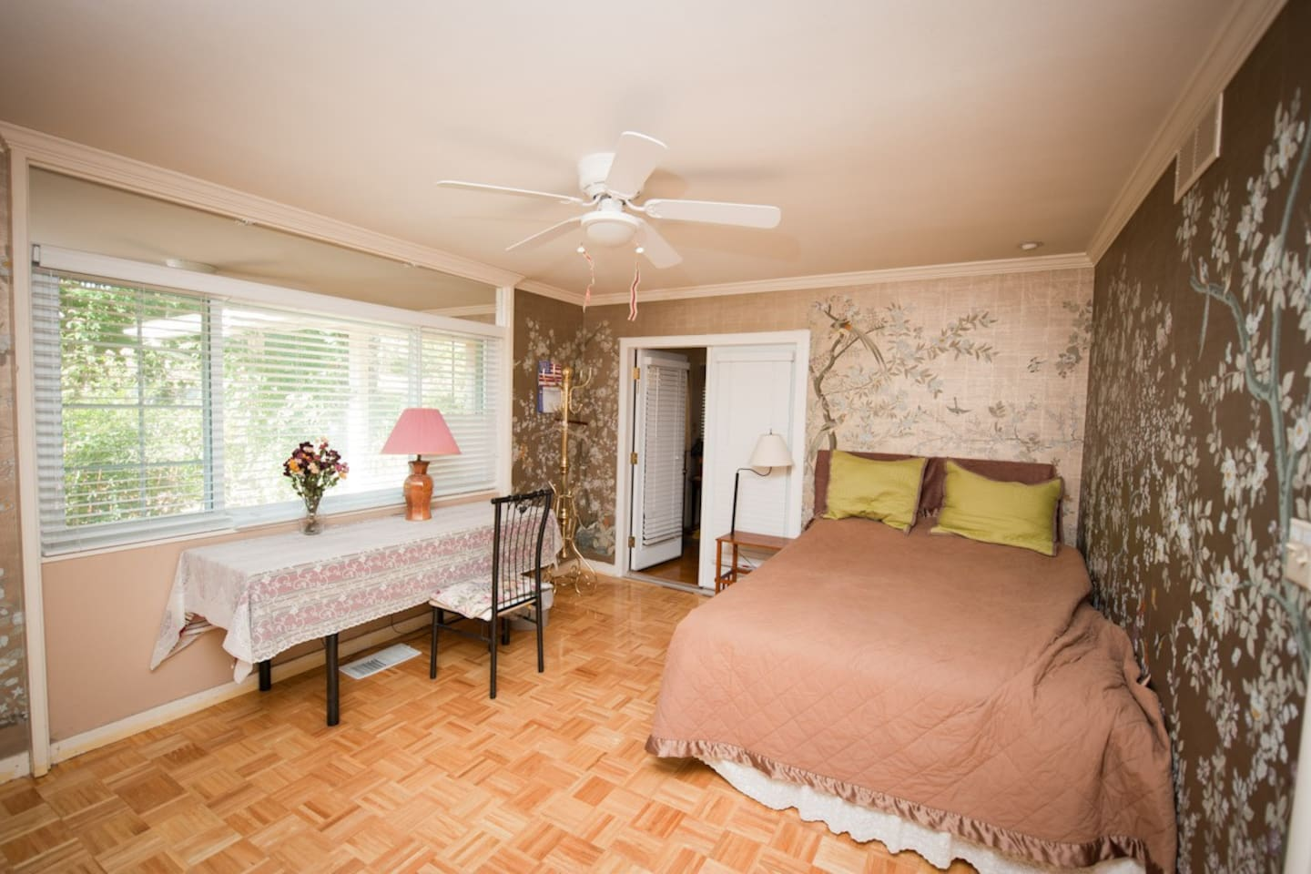 This main guest room has a queen size bed, a desk, and a small vanity table.  Through the big windows, you can see lots of flowers outside. This room is adjacent to a big living room and separated by a big panel which is totally closed from the host's quarter, very private.