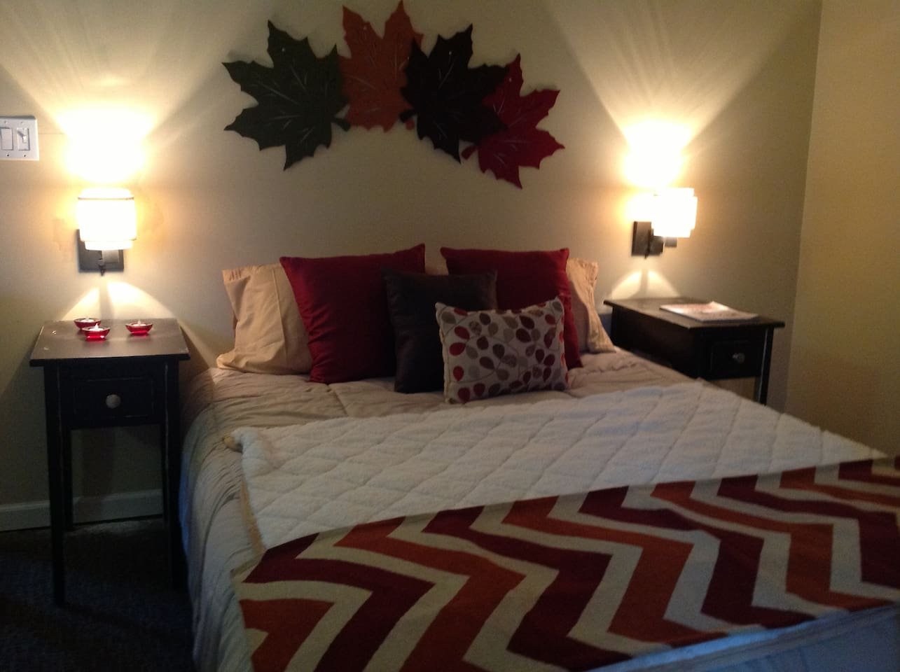 The master bedroom has a firm queen mattress accented by autumn colors.