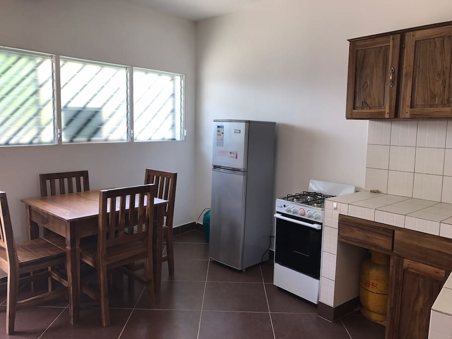 Large fridge/freezer, stove/oven, dining table, and fully equipped kitchen.