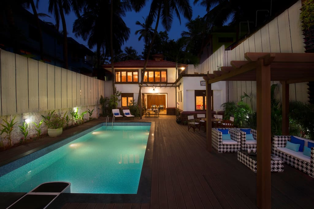 The swimming pool and deck area by night.