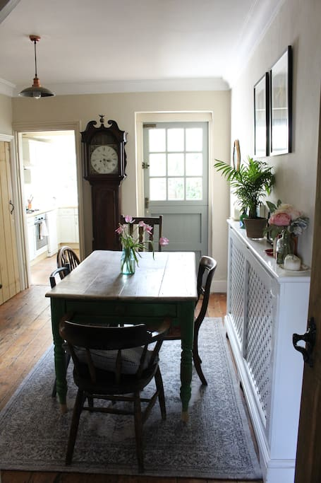 Dining room with open fireplace, wooden floor boards, seating for 6, and back door out to garden