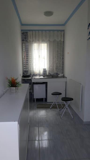 Fogão elétrico, frigobar, mesa articulada e cama de solteiro fechada