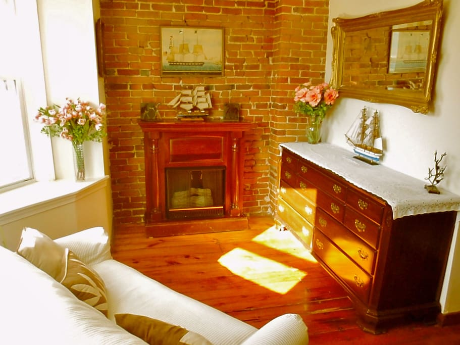 Sunny sitting area in bedroom wing of the apartment -cozy loveseat with fireplace and empty dresser to put your clothes away