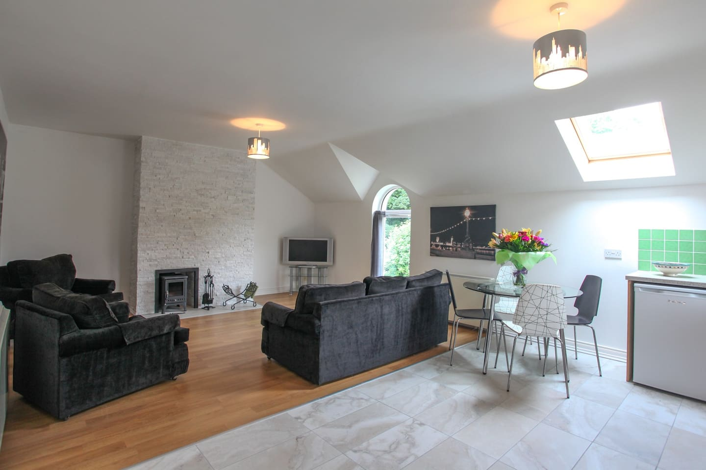 Spacious seating area with Peat burning stove and feature granite wall