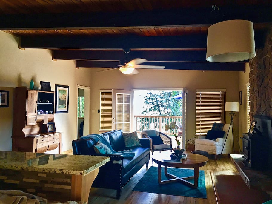 Cozy living room with French doors to  the pool, town lights & views of the lovely trees.
