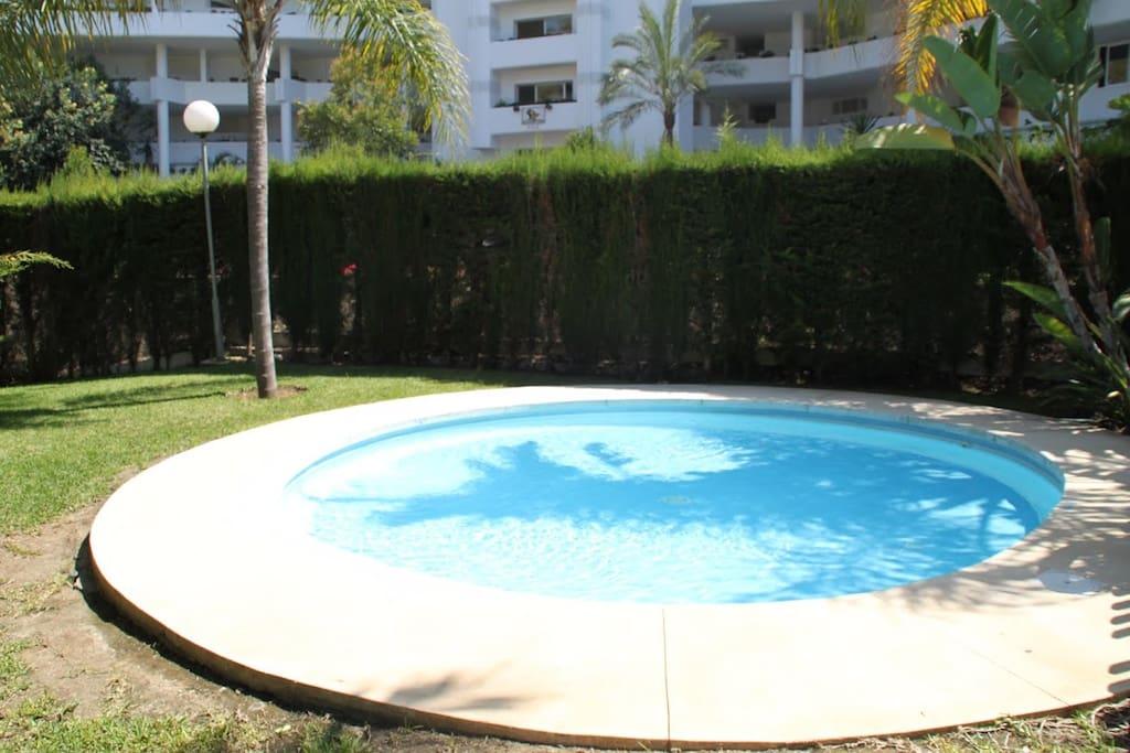 piscina de niños vallada con aérea de juego