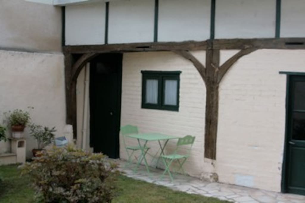 The garden area with a table and chairs for enjoying coffee and croissants, an evening aperitif, or anything in between