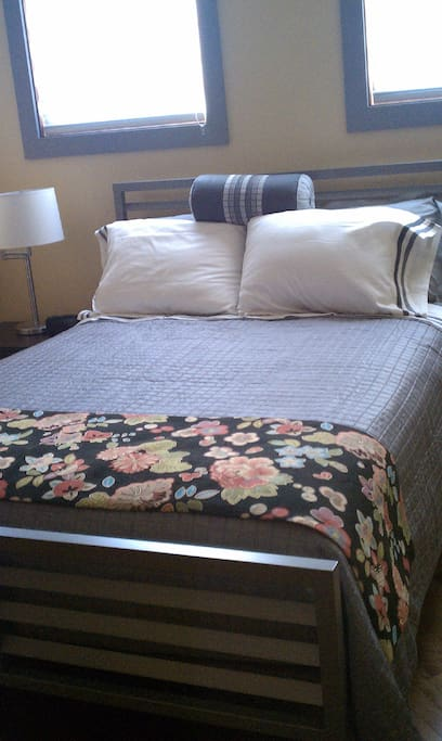 Sleeping area features a queen bed and a nightstand w/lamp.