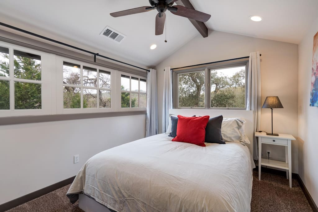 """Red Room"" with a queen bed, flatscreen TV, luxury pillows and linens and a view of beautiful oak and incense cedar trees"