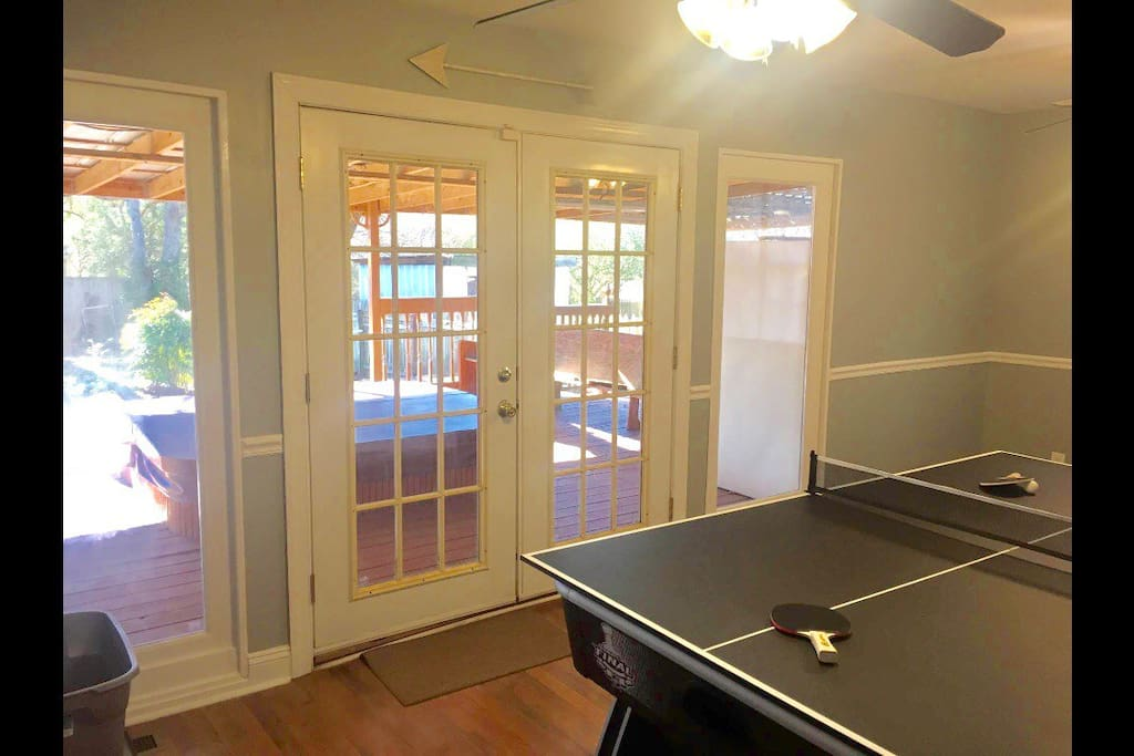 Game Room with Air Hockey/Ping Pong and Foosball as well as a Vinyl Record Player overlooking the backyard, deck, and hot tub