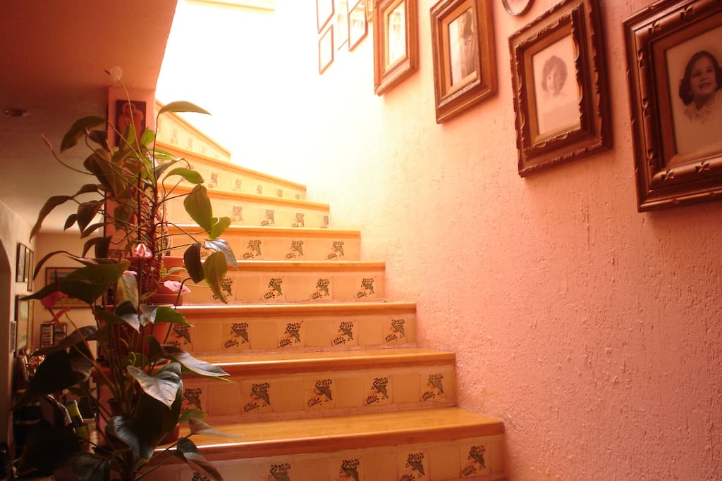 View of hand painted tiles on stairs which go up to bedrooms on second floor.