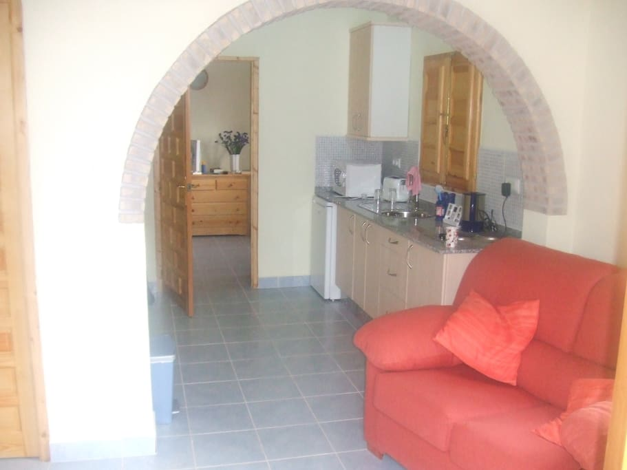 This photo shows the lounge and kitchen areas with the rear door leading to the bedroom.  There is a 2 ring hob with microwave oven.