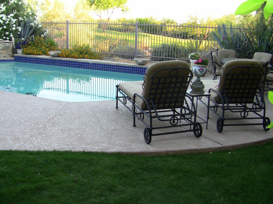 view of golf course from 6-seat outdoor table and lounge chairs view