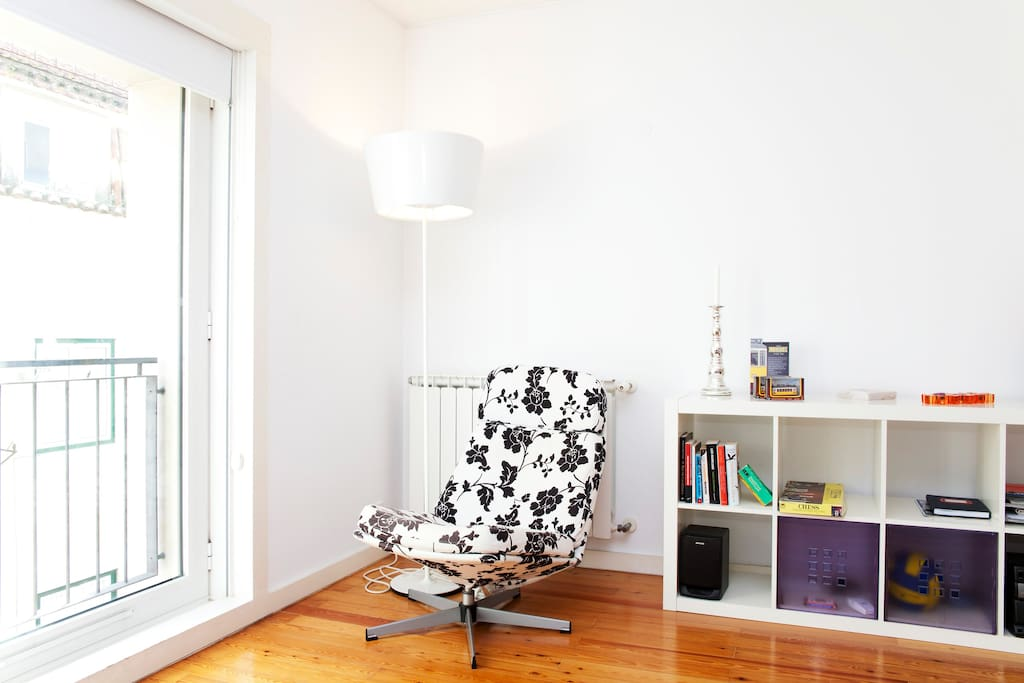 Wide window and a poltrone for reading Time Out Lisbon that is available at the apartment