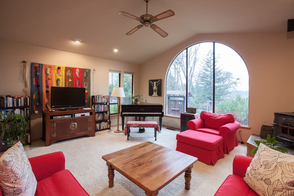 Living room wtih baby grand piano, flat screen TV, wood-burning fireplace