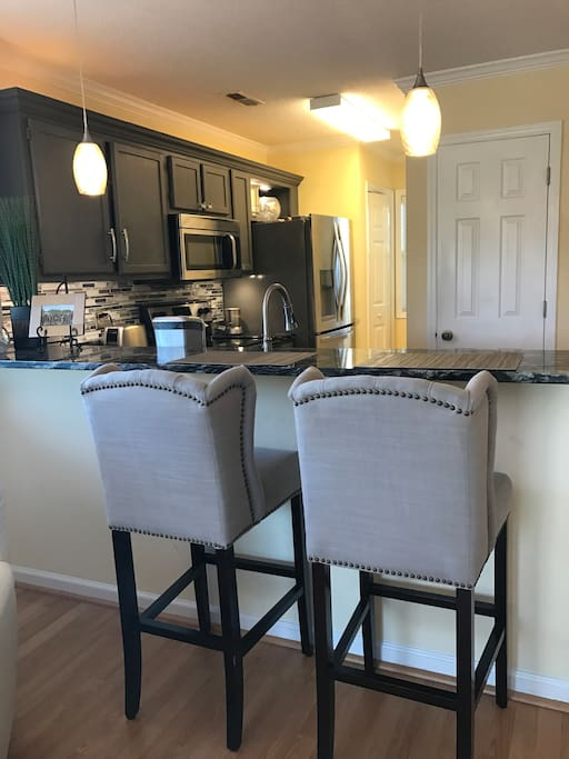 Comfortable upholstered bar stools with granite countertops and high bar.