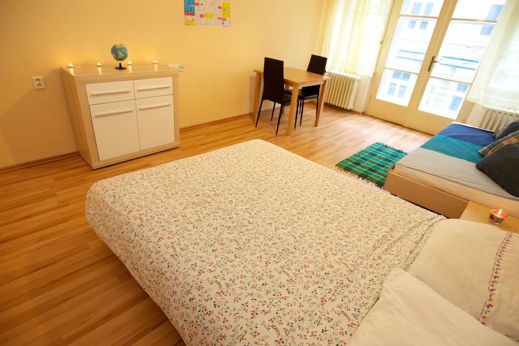 The room contains one double bed, one single bed, a table with chairs, dresser, small night table, wardrobe closet, and large windows offering lots of light.